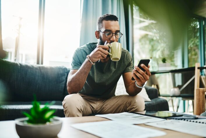 Man using a 5G phone while drinking his morning coffee