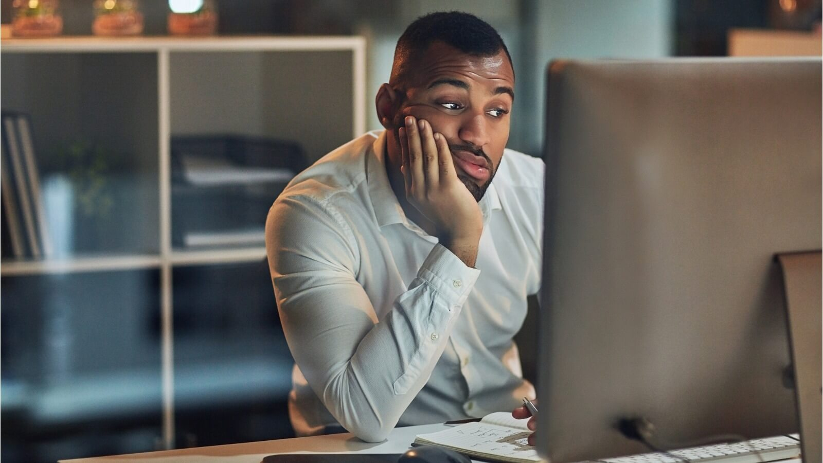 Man staring at computer screen with frustrated look