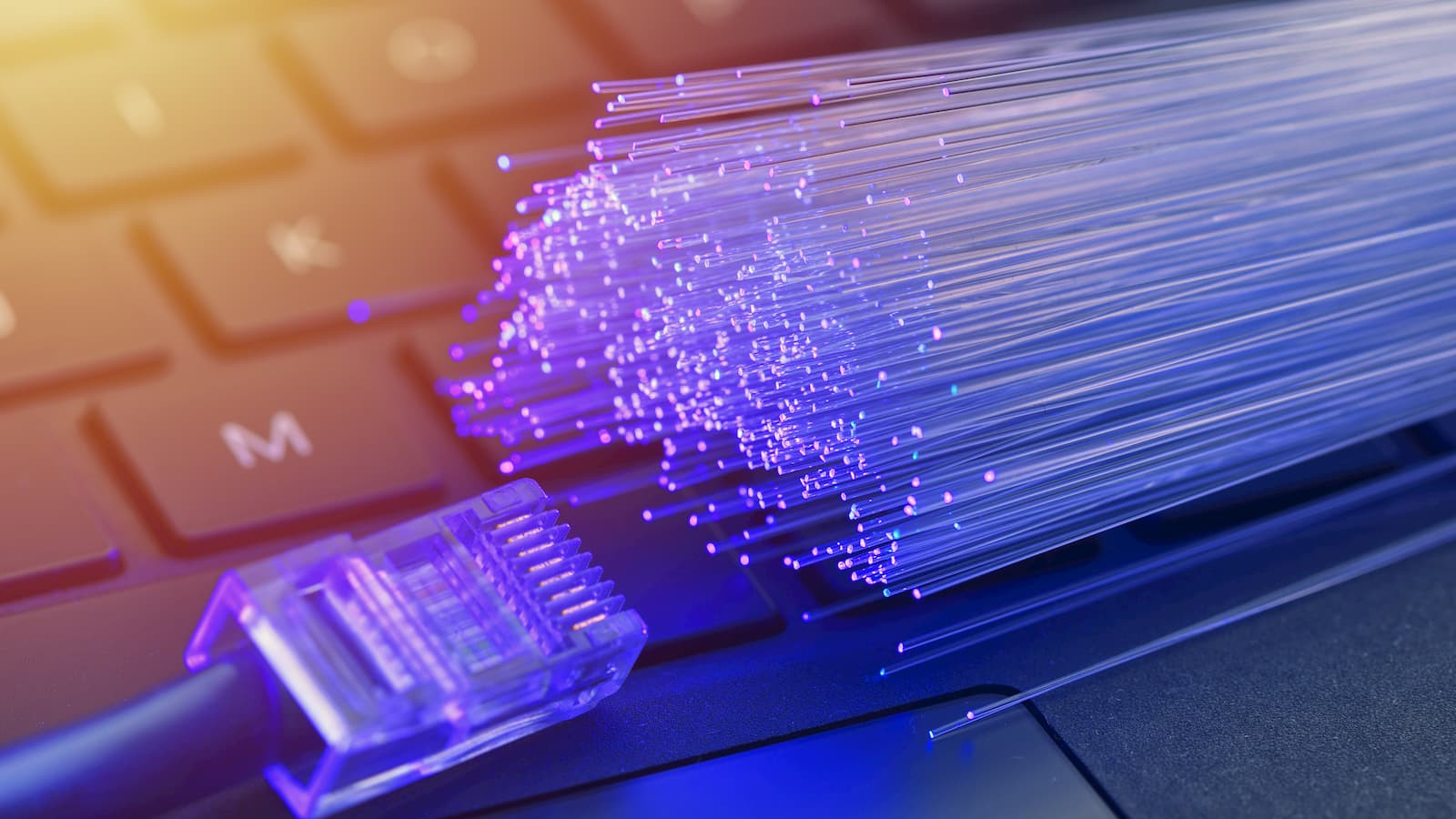 An image of optical fibers and an ethernet cable lying on a keyboard.