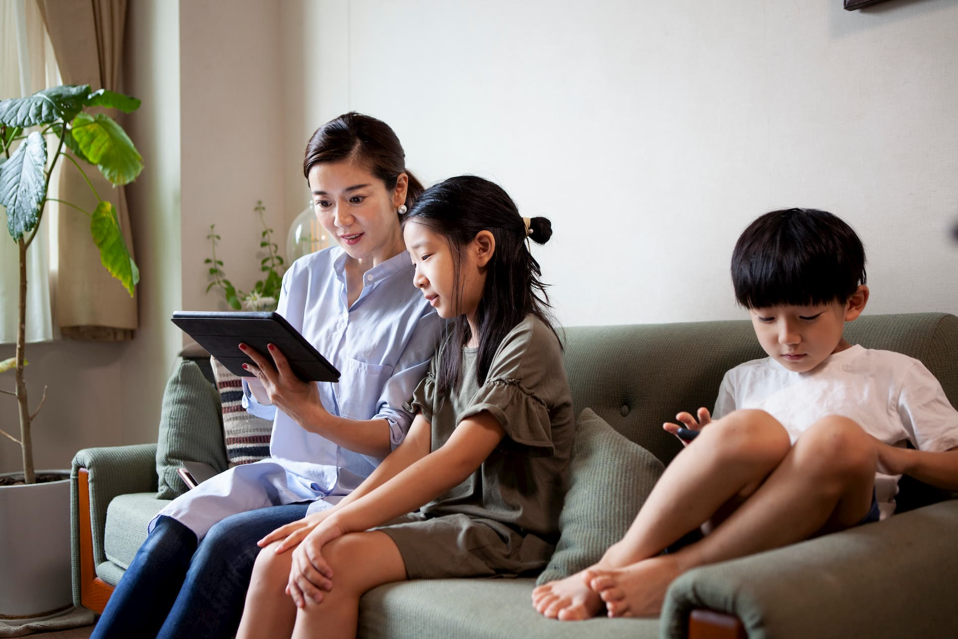 A mom and two kids on their tablets