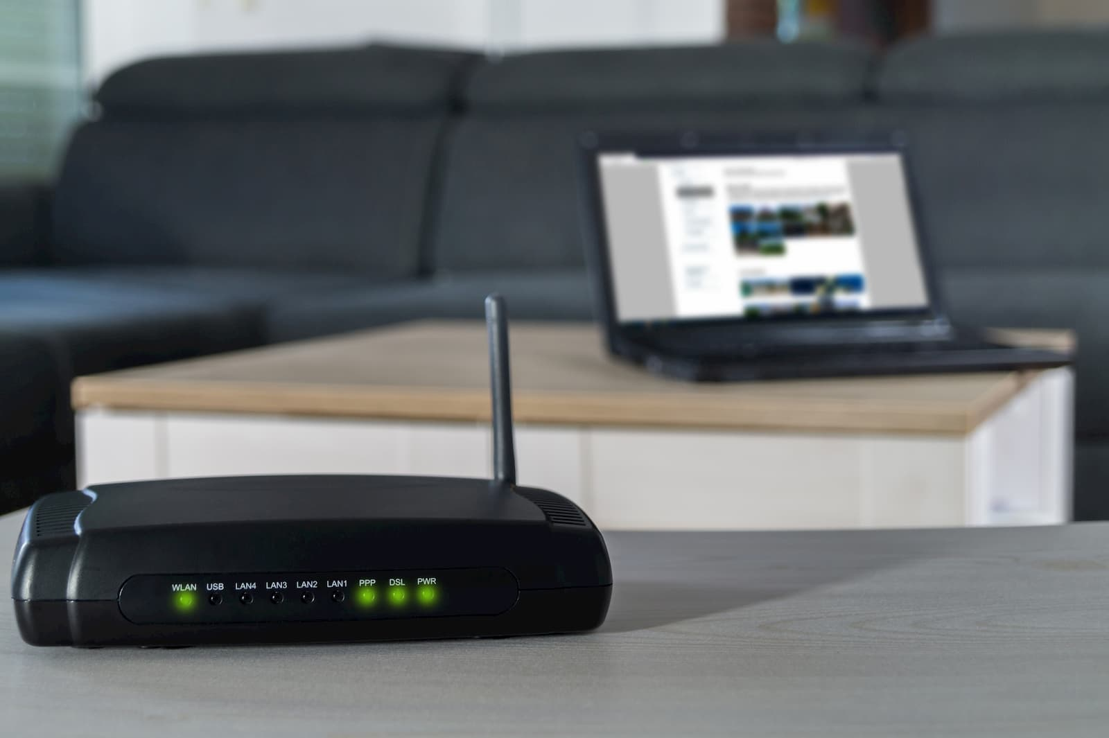 router sitting on a table near a laptop
