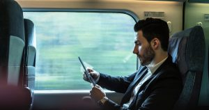 man using tablet on train