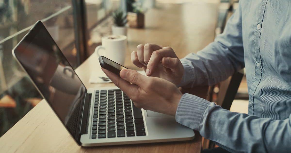man sitting at his laptop using a phone