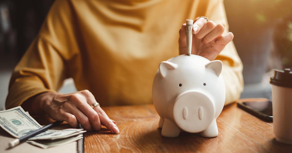 A senior citizen putting money in a piggy bank.