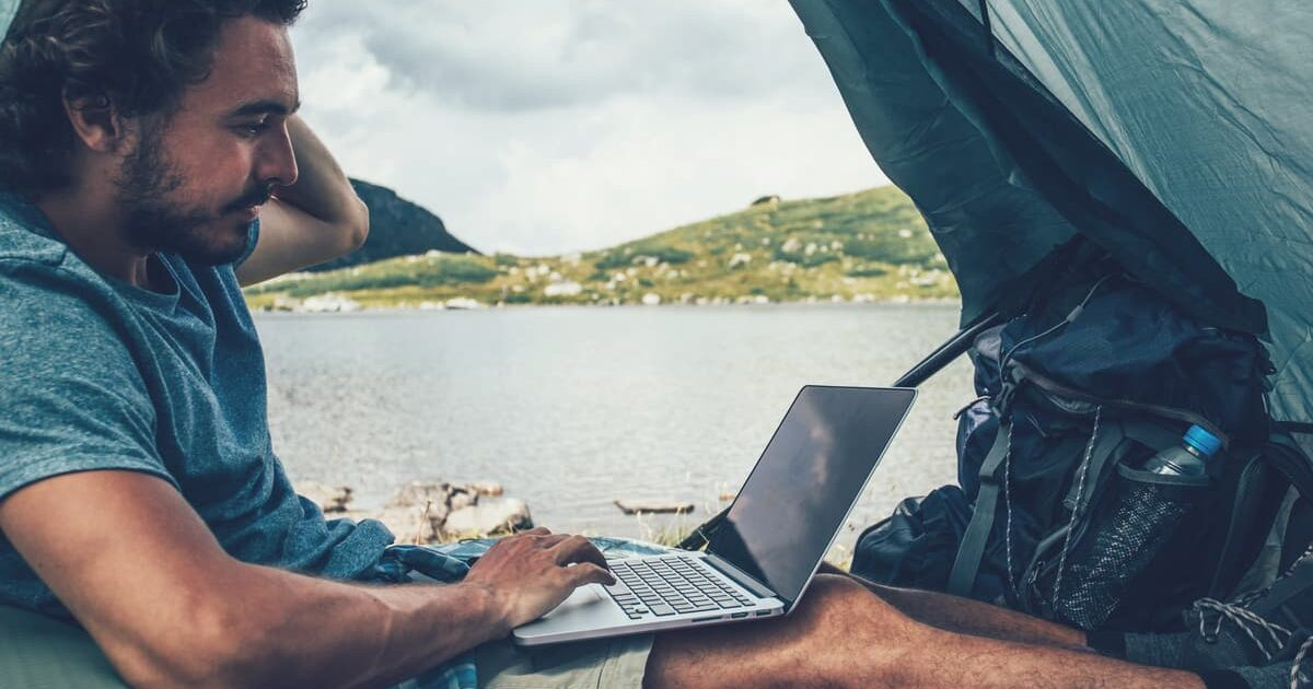 man using a laptop in a tent near a lake