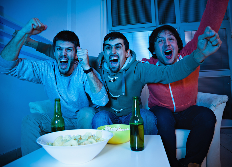 A group of friends are watching television. They have their arms thrown into the air, and there are snacks and beer on the table in front of them.